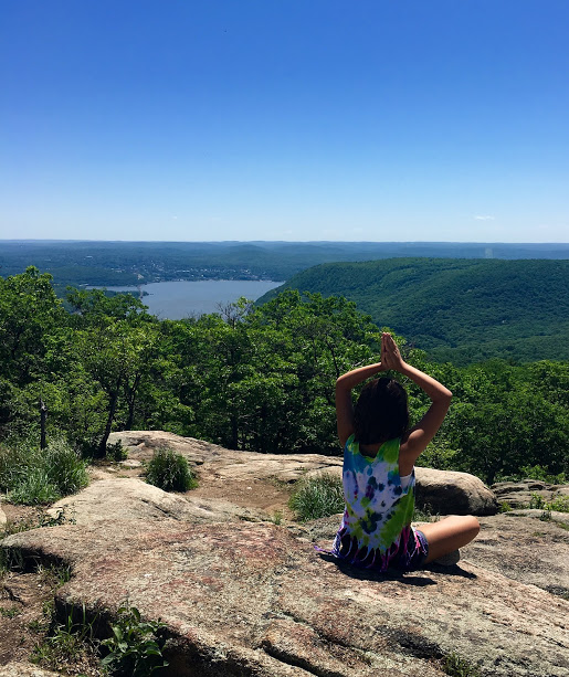 Brooke meditating and doing yoga at Bear Mountain State Park in New York